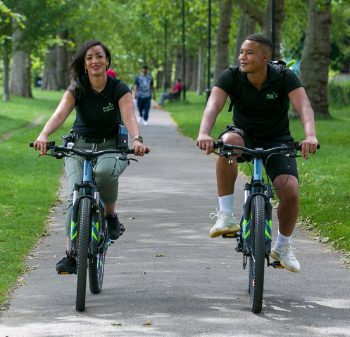 A man and a women cycle in a park
