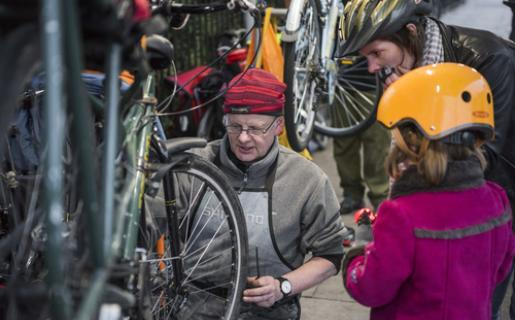 Bike mechanic fixes bike for child