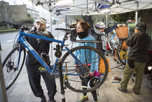 Bike mechanic fixes bike for Woman