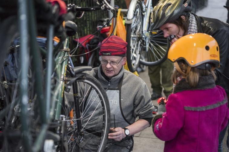 Bike mechanic fixes bike for Child