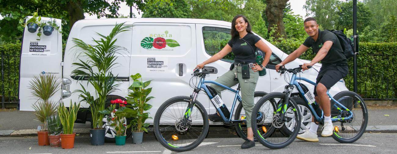 A woman and a man stand next to bikes, a van and plants