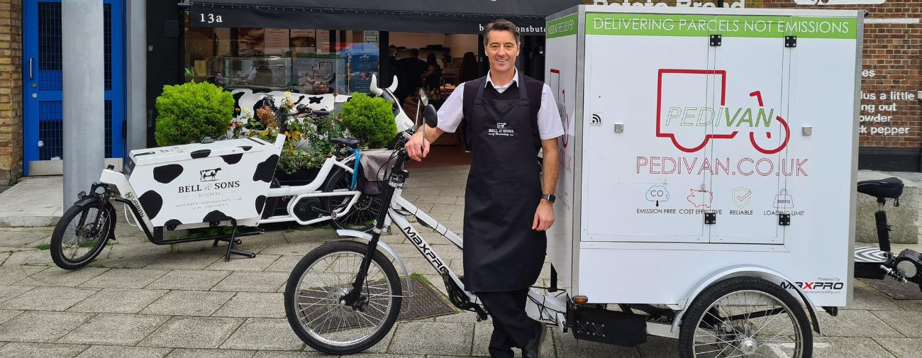 A smiling man stands in front of a large cargo bike which says 'Pedivan' on it