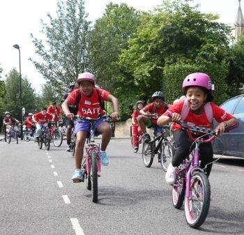 a large group of children cycle down a road