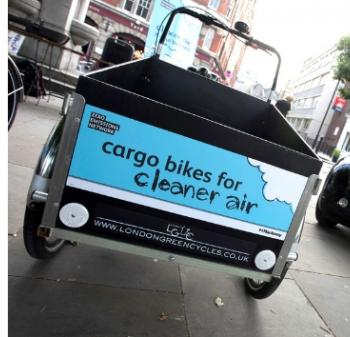 black cargo bike with blue sign on it saying 'cargo bikes for cleaner air' with ZEN logo and logo from London Green Cycles