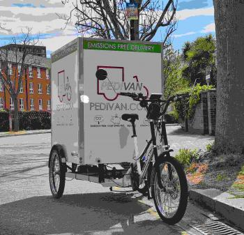 A large white cargo trike - with a big box on the back and the word 'Pedivan' on it on the road